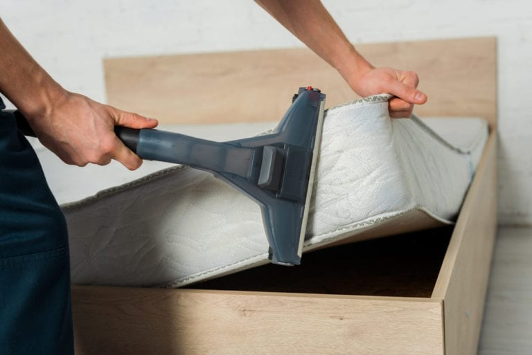 Man Removing Dust From Mattress
